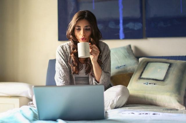 Frau mit Laptop und Heißgetränk auf Bett sitzend, Nutzung von Elektronikgeräten und Koffeinhaltige Getränke vor dem Zubettgehen können zu Schlafstörungen führen.